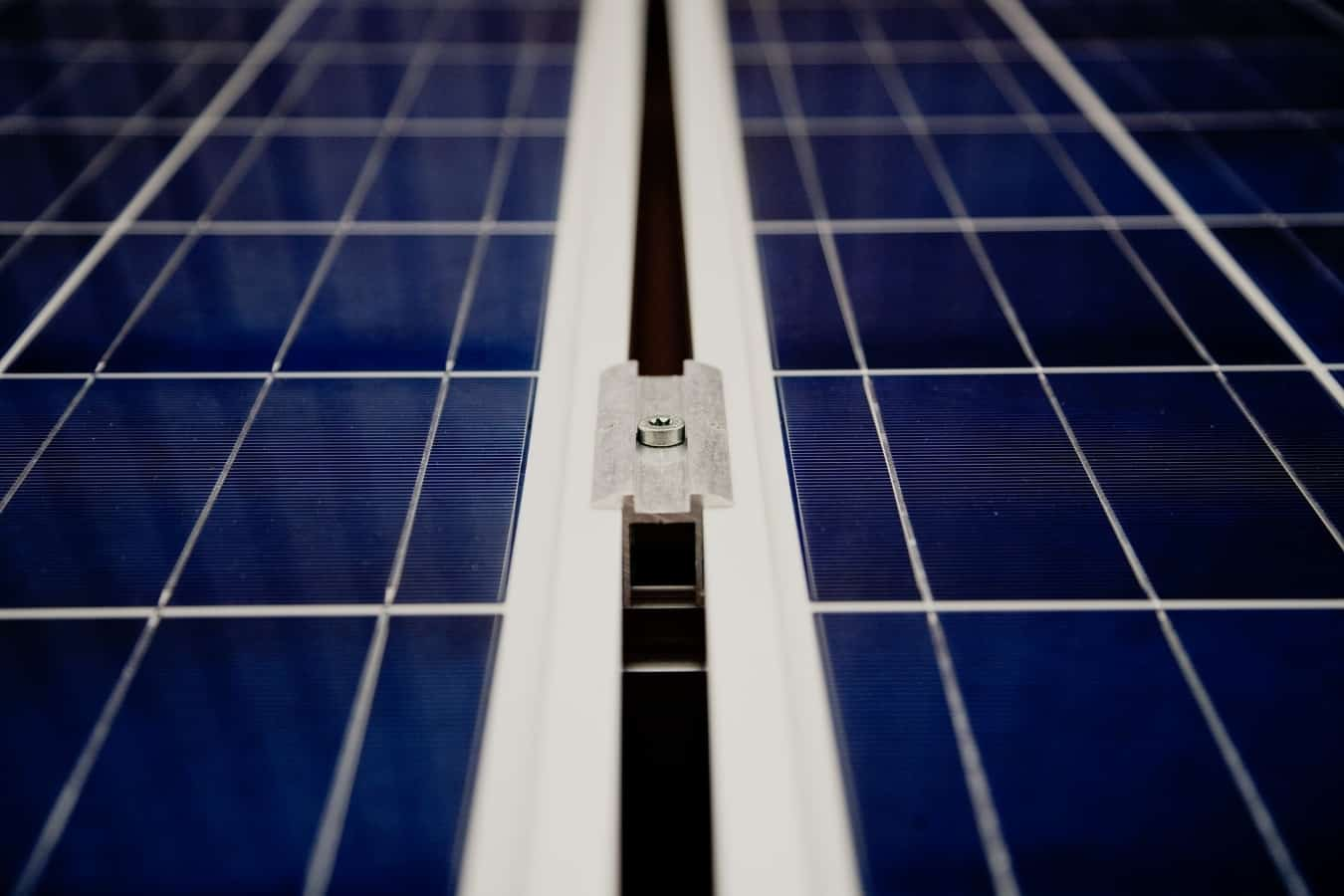 A closeup of dark blue solar panels and a white mounting component between the grids.