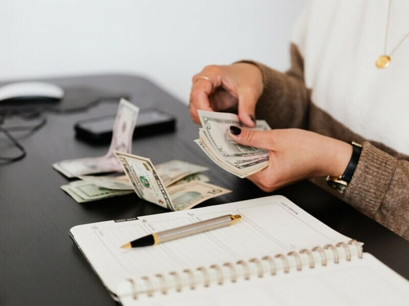 A woman counting through money on a black table that also holds her planner and cell phone.