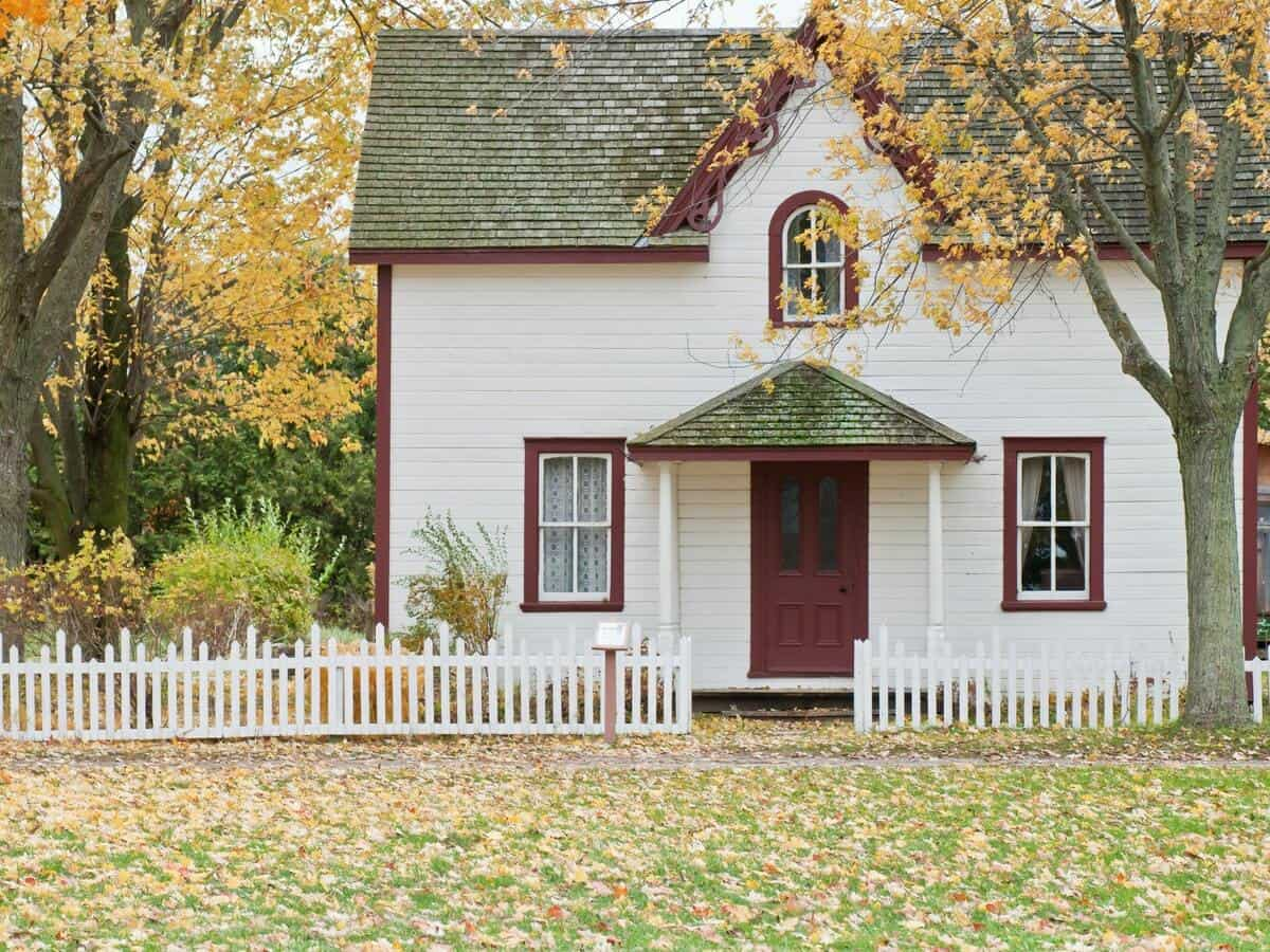 A small, two-story home with white paneling is next to trees with orange leaves in the fall.