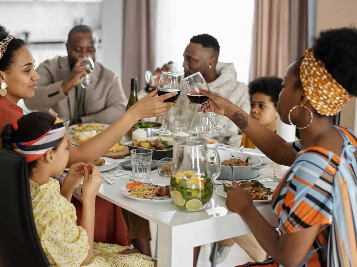 A large family sits at the dinner table for a meal.