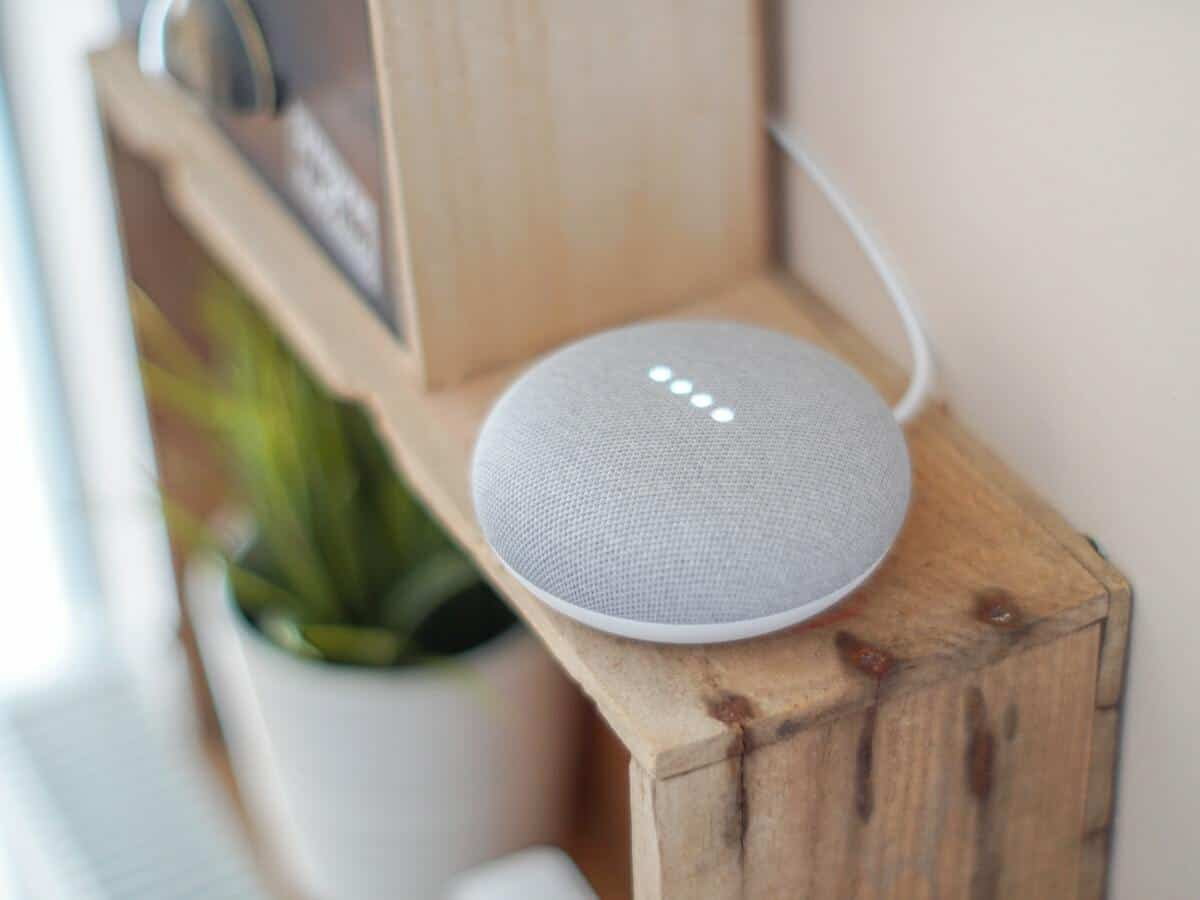 A grey google home mini sitting on top of a brown wooden bookcase.