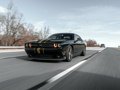 A black Dodge Challenger driving down a road on an Autumn day.