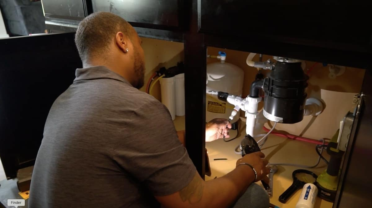 An ONIT water expert is installing a filtration system for hard water treatment at home.