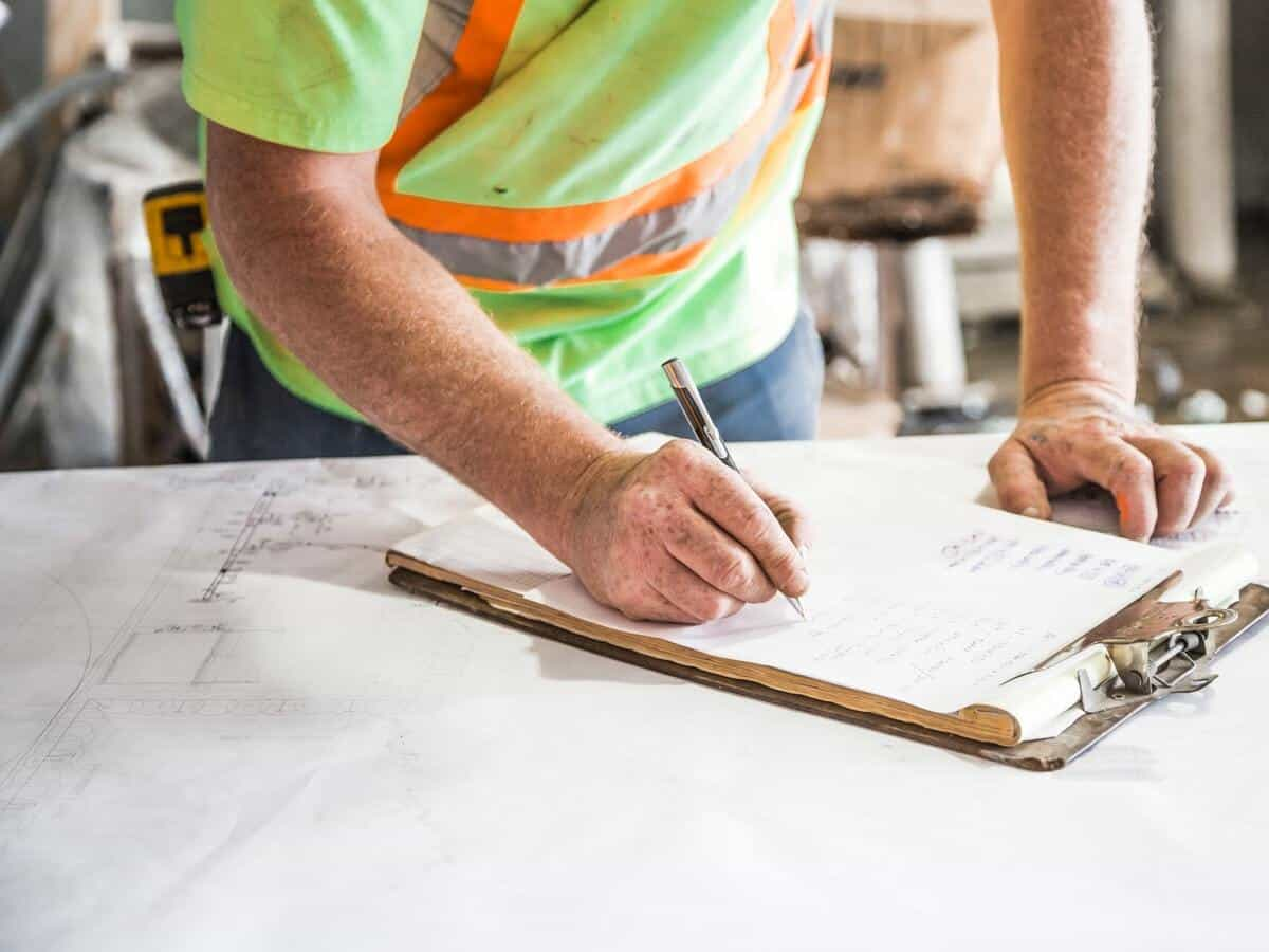 A roofing and construction worker filling out a tracking sheet that's on top of a clipboard on a table.