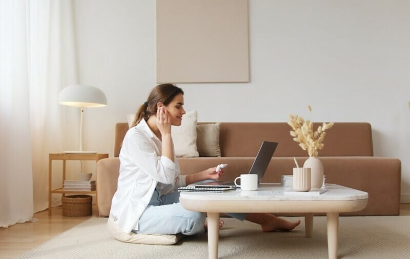 A young woman sitting on the floor of her living room as she puts on her cordless headphones and works from her laptop.