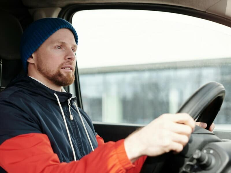 A man dressed in winter clothes has his hands on a black steering wheel as he drives a vehicle.