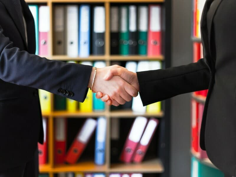Two adults dressed in professional clothing shake hands in a work setting.
