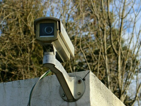 An outdoor security camera installed on a cement building that sits in front of trees.