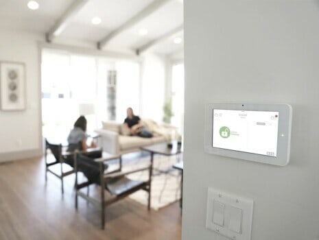 A white Qolsys IQ2 Panel installed in a family's living area.