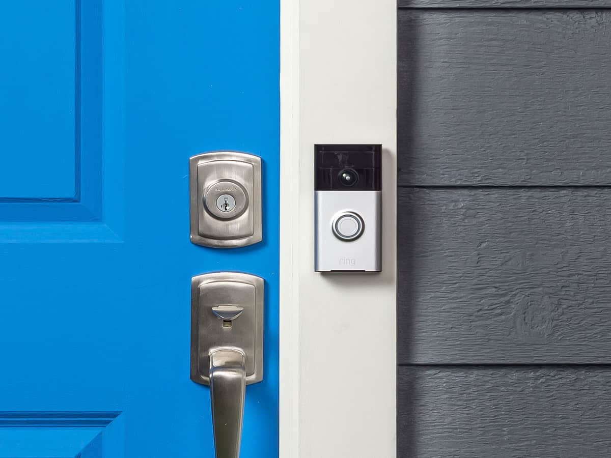 A Ring doorbell camera installed next to a bright blue front door.