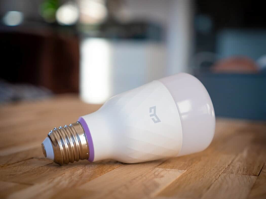 A smart bulb lying on a brown wooden kitchen table inside of a home.