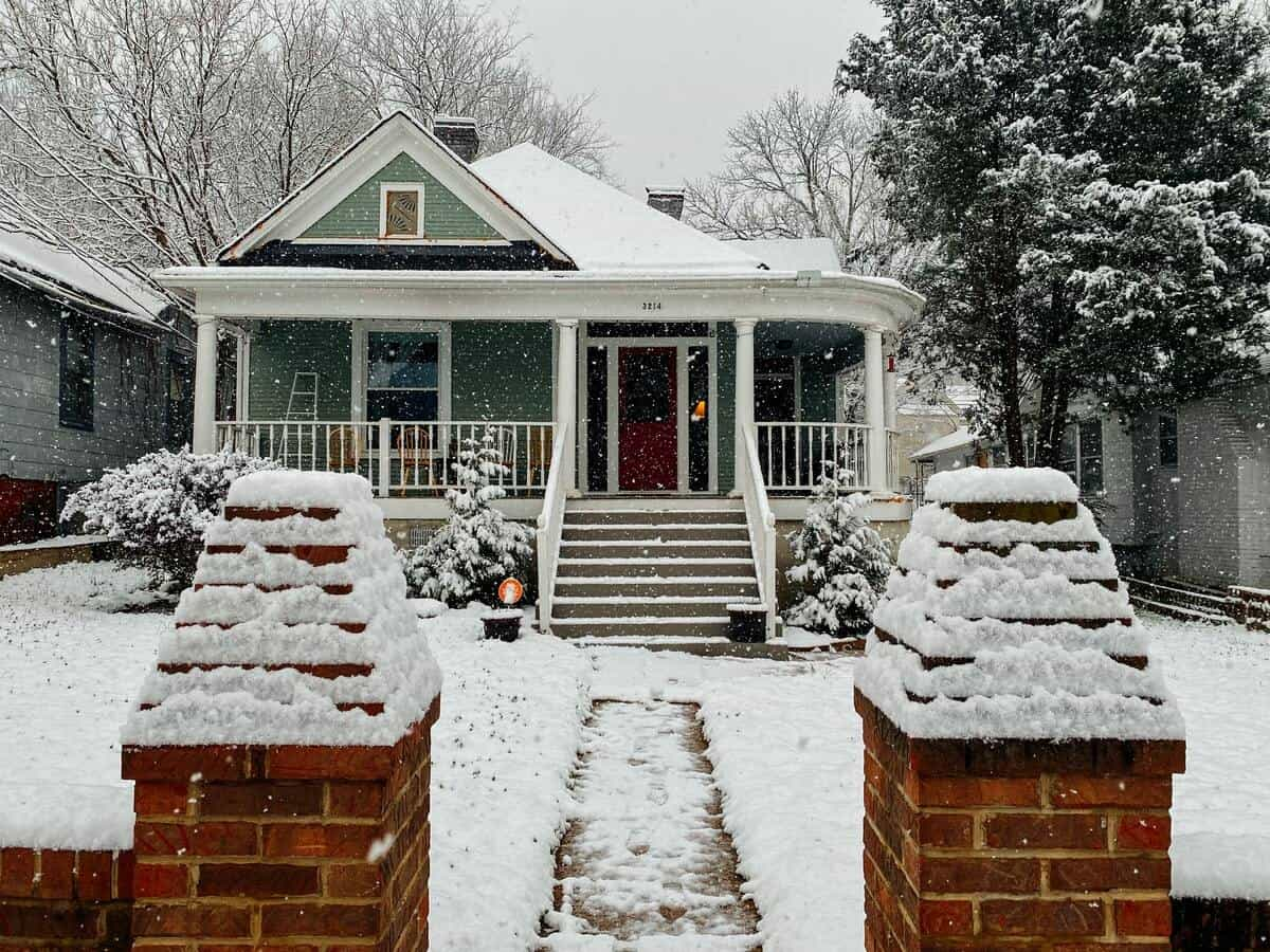 A craftsman style home surrounded by snow.