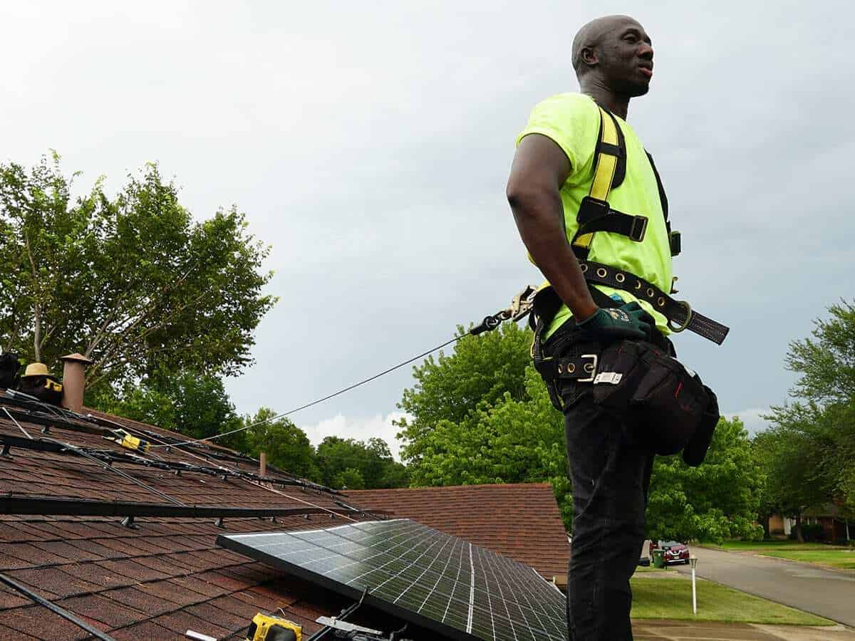 An ONIT Home Service solar panel technician expert standing on a roof during installation.