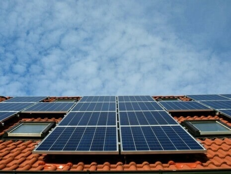 A view of a Spanish style roof with solar panels and the sky above it.