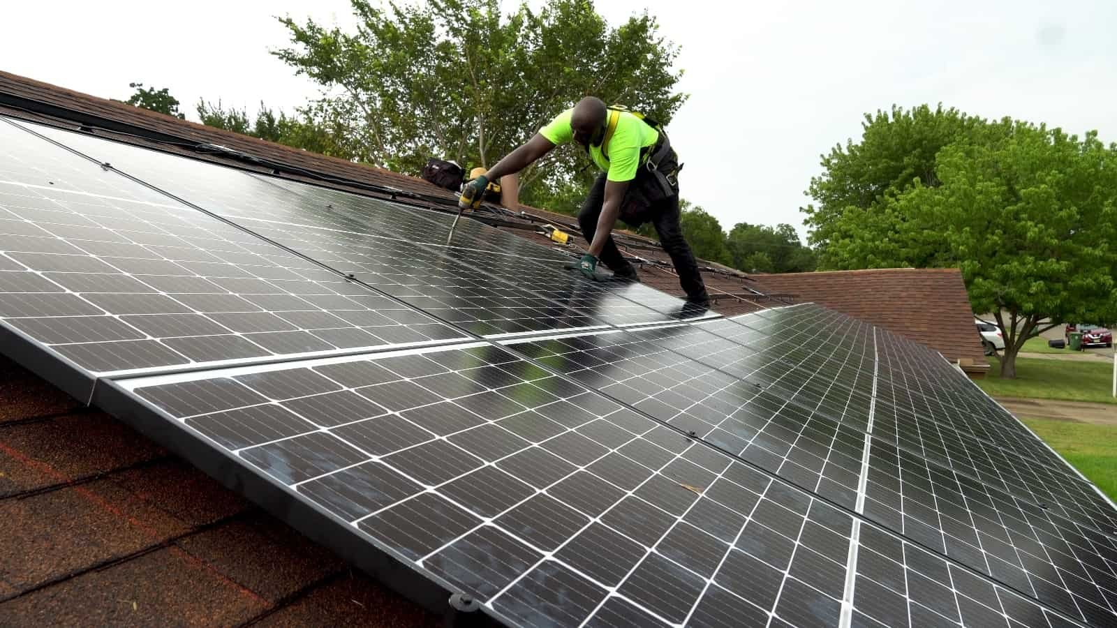 A man is installing solar panels on top of a roof.