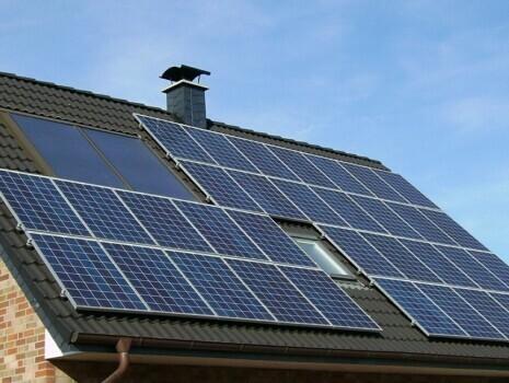 Dark blue solar panels installed on a black metal slate roof.