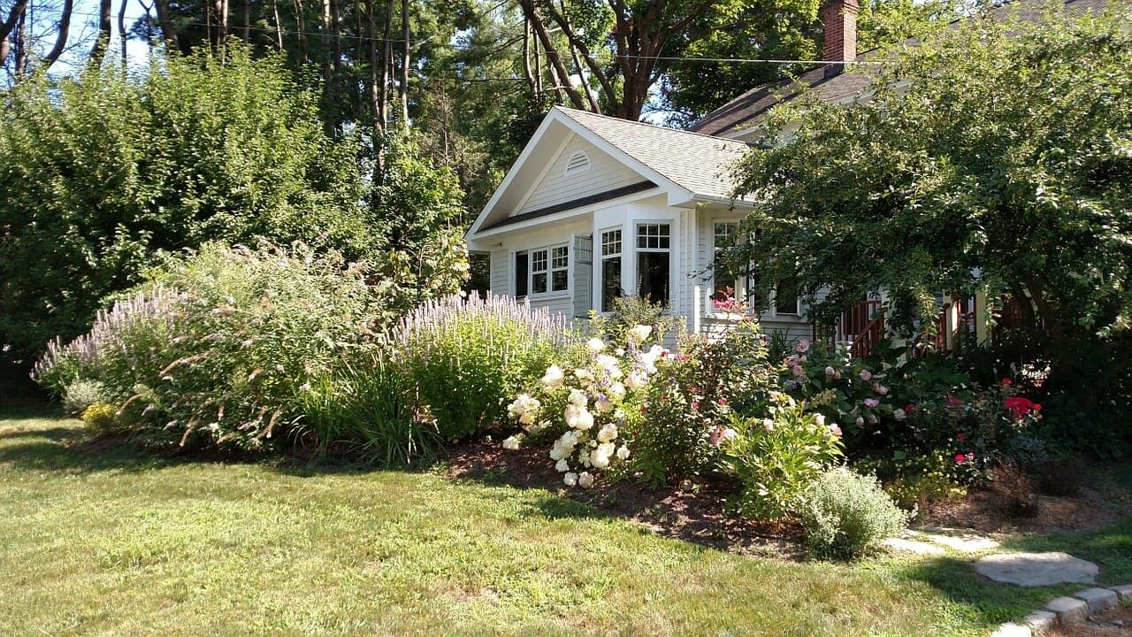 An American craftsman home surrounded by trees and beautiful floral landscaping.