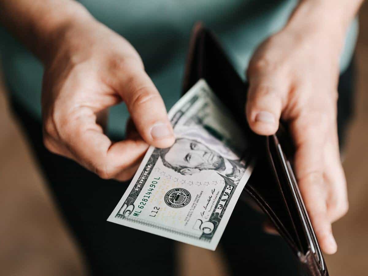 A man is pulling a five-dollar bill out of his wallet.