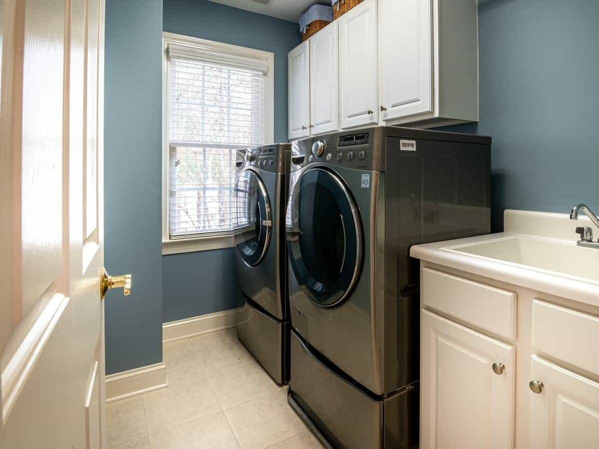 A washing and drying machine inside of a home's laundry room.
