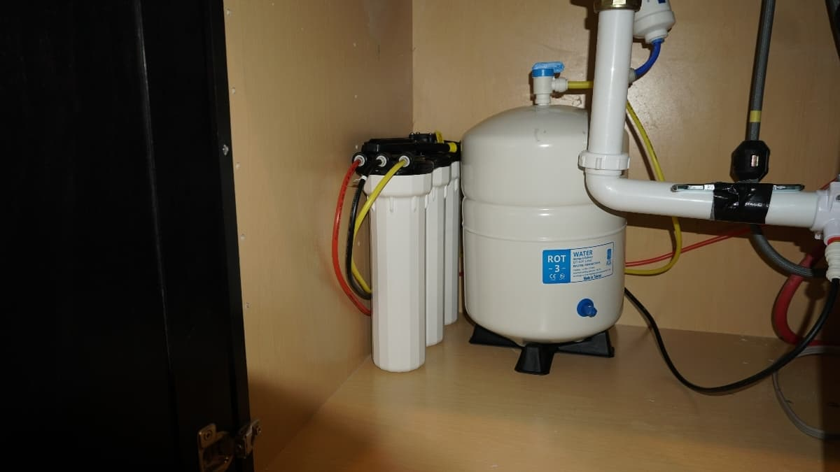 A whole home water filtration system installed under a kitchen sink.