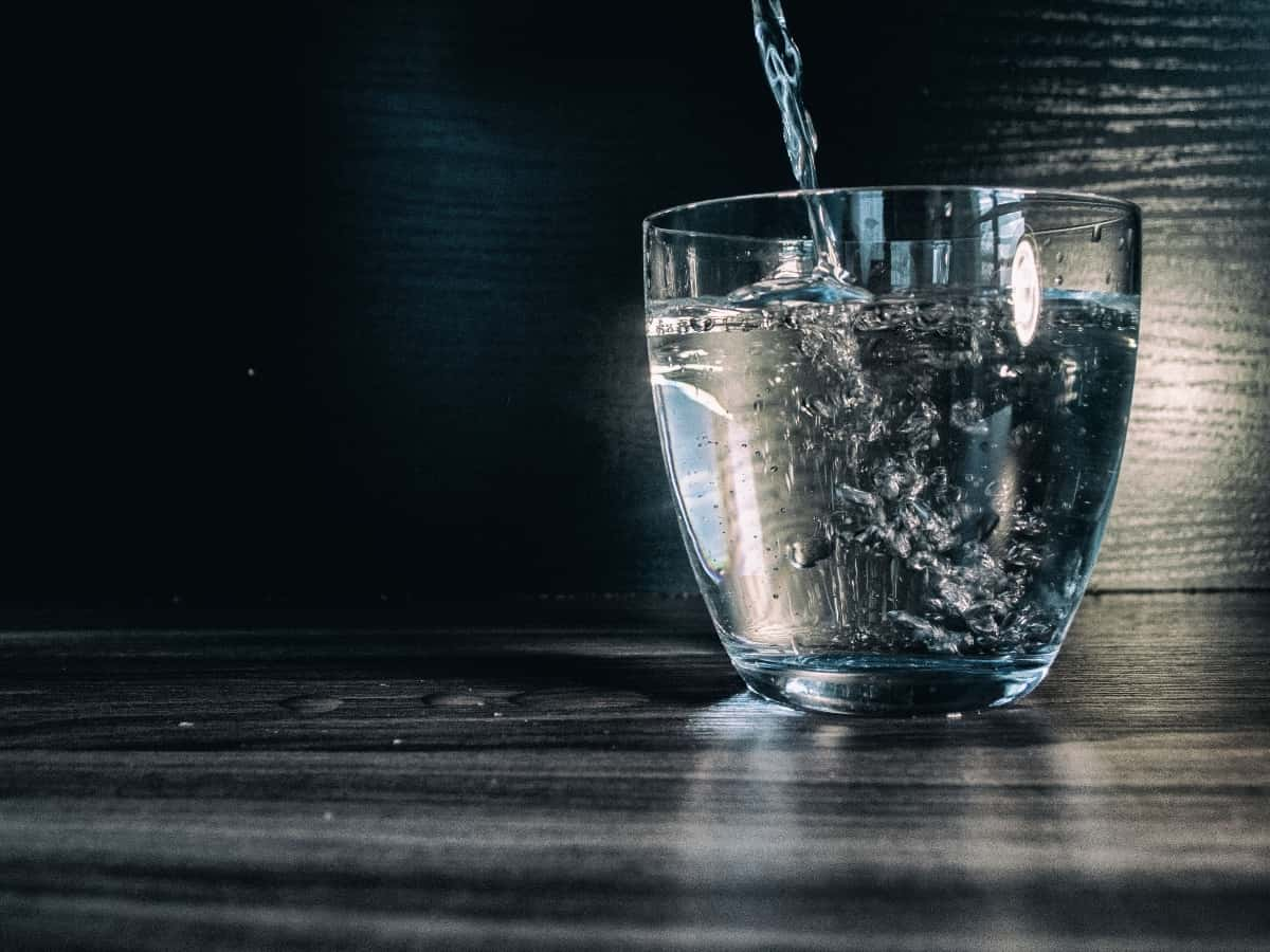 Water pouring into a modern, glass cup sitting on a dark wooden surface.