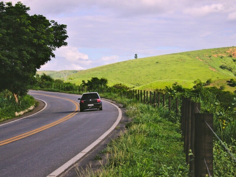 The back of a black Volkswagen Golf driving down a winding road on a countryside.