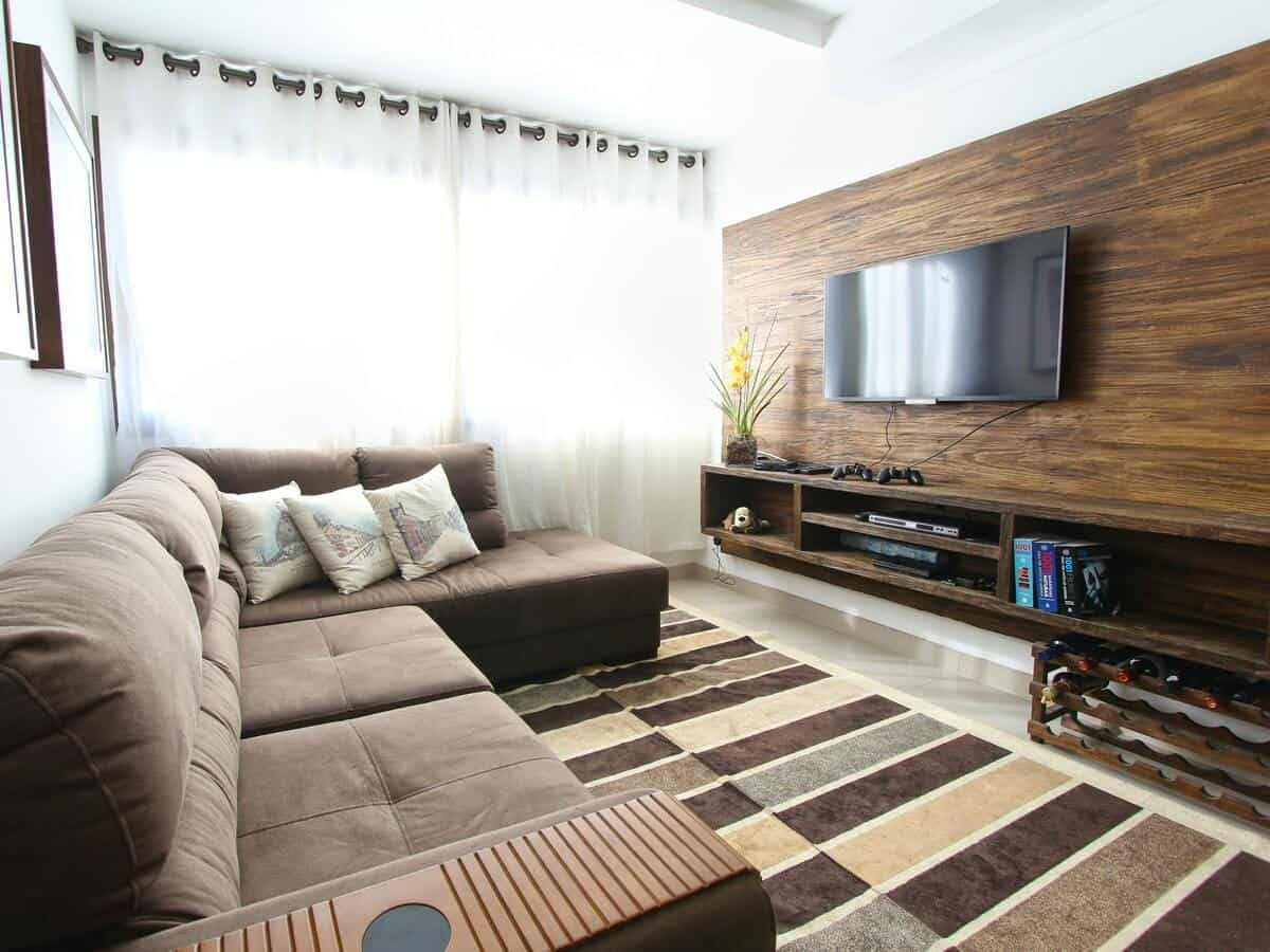 A modern living room with a brown sofa and a brown wooden paneled accent wall holding a flat screen television.