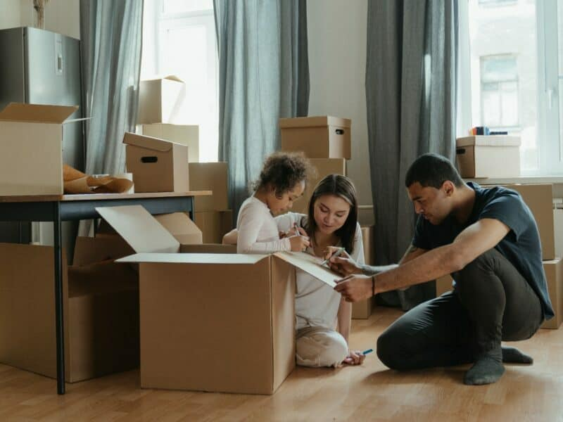 family unpacking, mom dad and child surrounded by boxes