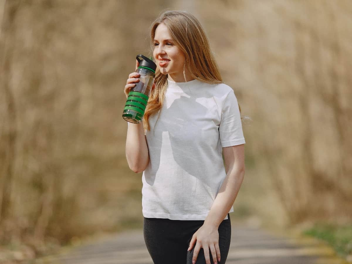 woman with light brown hair wearing white shirt and leggings drinking out of green bottle