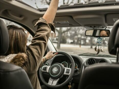 A young female driver has her right arm up through her vehicle's sunroof as she sits behind the wheel.