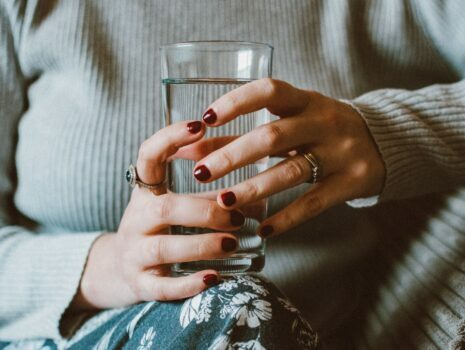 A woman with dark red fingernails is holding a glass of water on her leg.