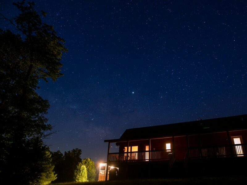 A cabin lit up with outdoor lights against a dark night sky.