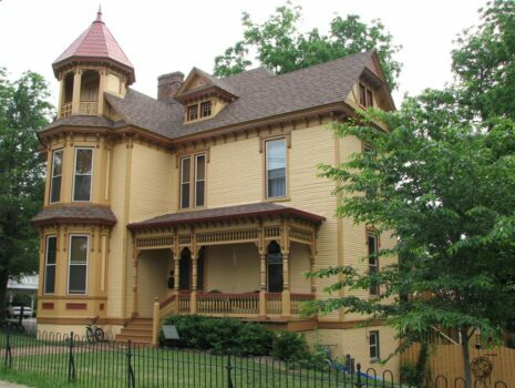 an older home on a corner, victorian style, brown home