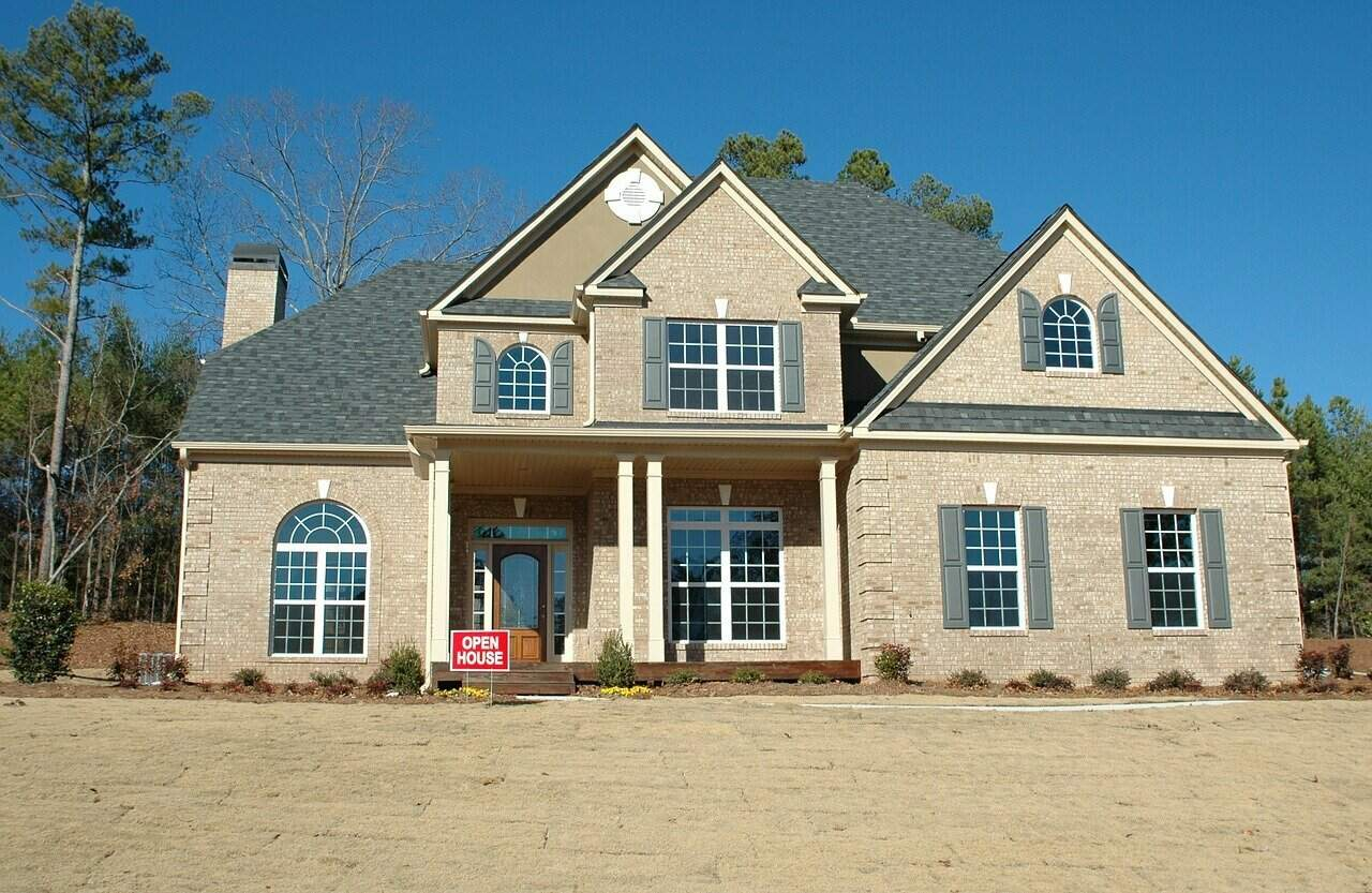 """A two-story suburban home with a red """"open house"""" sign on the front lawn."""