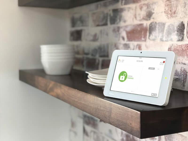 A Qolsys IQ Panel sits on a wooden shelf that's against a brick wall.