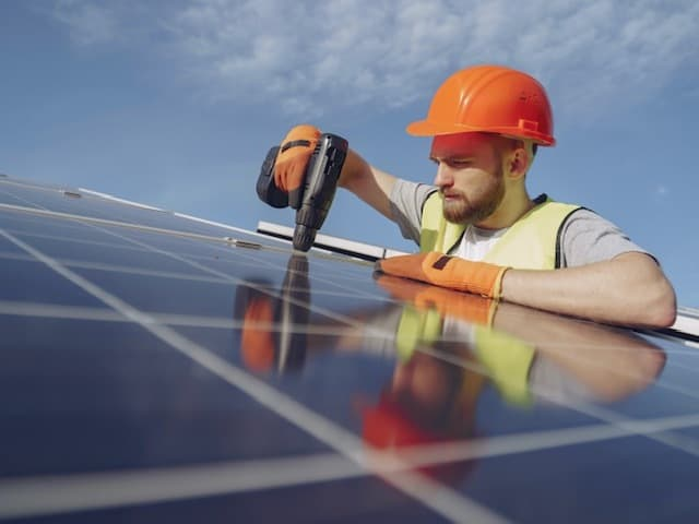 installation of solar panels guy in orange hard hat and yellow vest