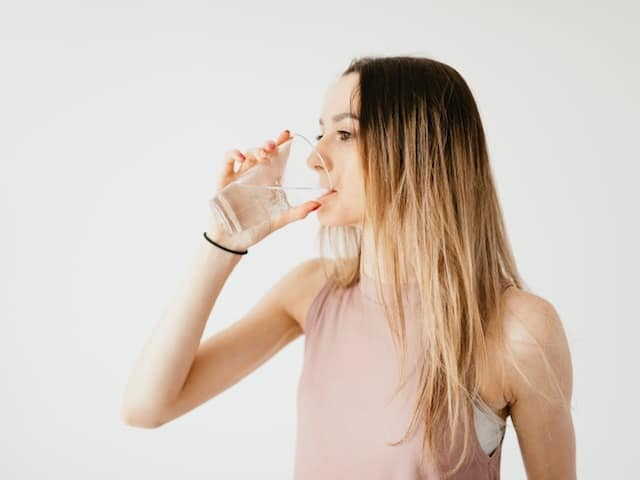 girl in pink shirt drinking water looking left