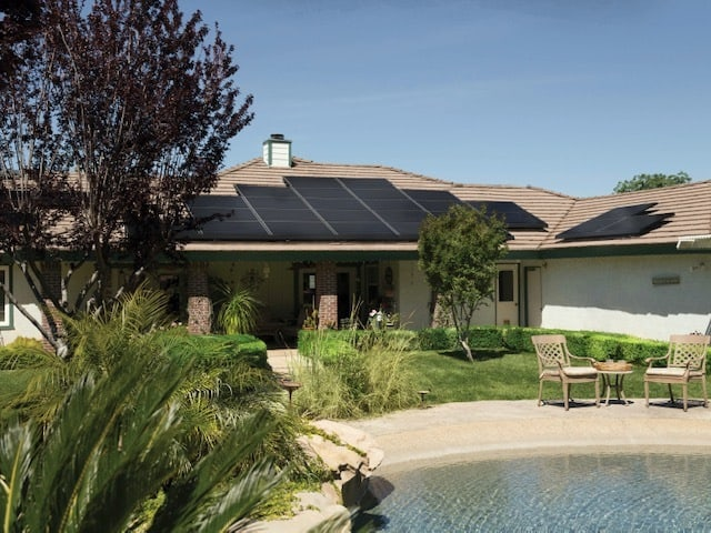 one story home with pool solar panels on roof