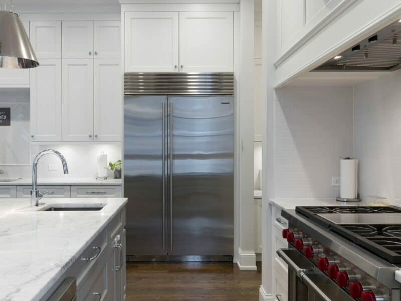 A stainless steel refrigerator and gas stove inside of a kitchen with white fixtures.