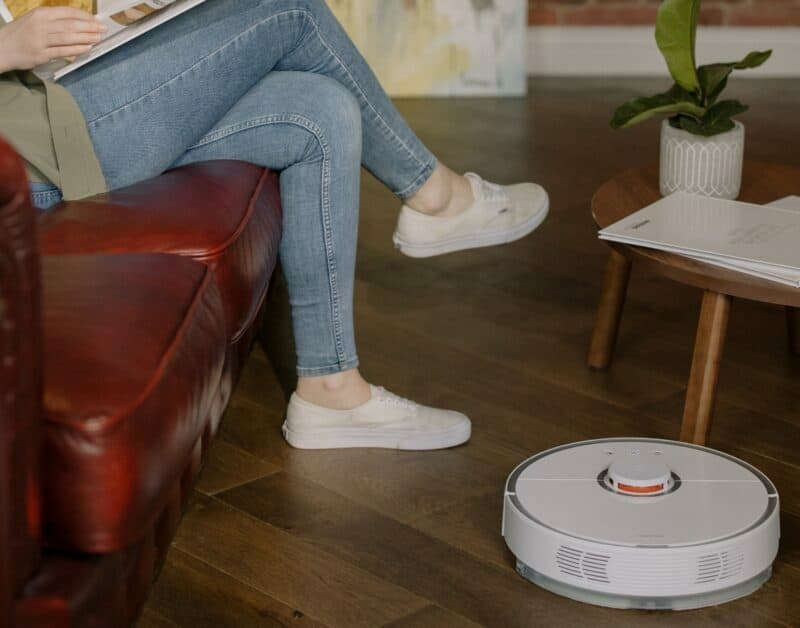 A woman sitting on a red leather couch is automating the cleanup in her home with a white robot vacuum.
