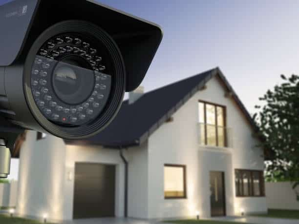 home security camera on left, white house with large windows on right side