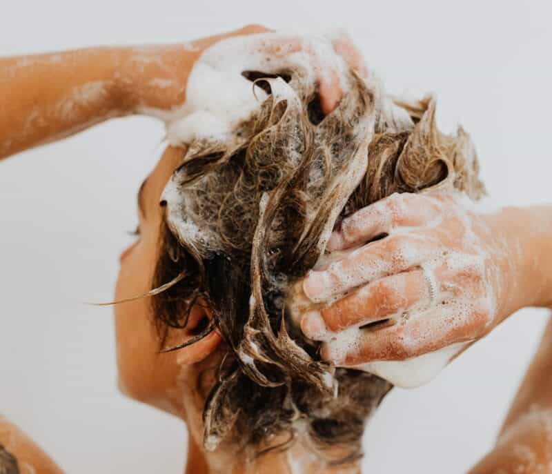 Soap suds in a woman's hair as she shampoos her strands.