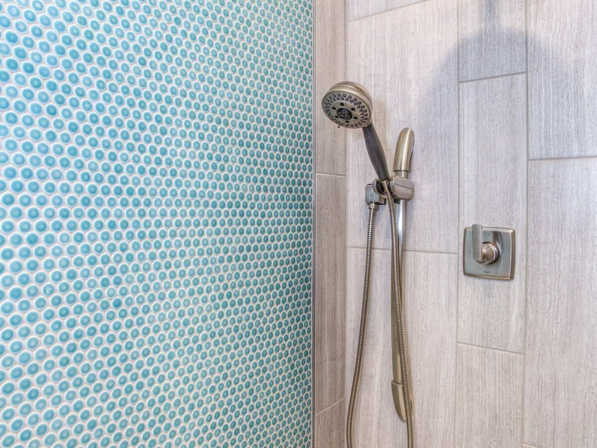A silver showerhead inside of a bathroom shower with bright blue tiling on the wall.
