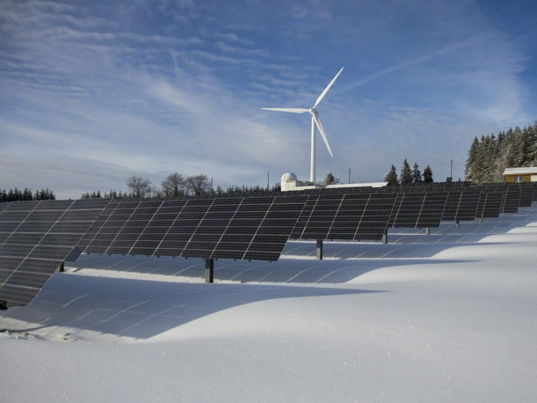 solar panels with wind energy in the background snow on ground and both renewable energy resources
