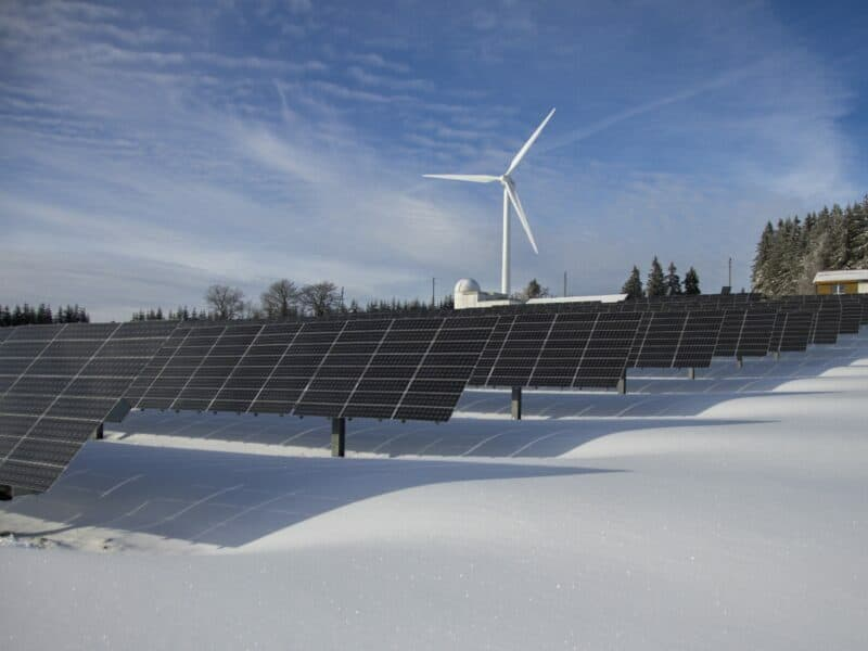 solar panels with wind energy in the background snow on ground
