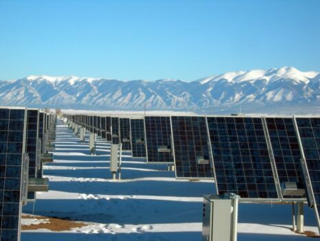 solar panels with a blue sky and mountains in the background