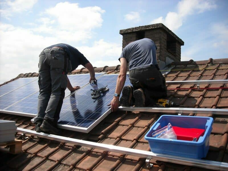 Two men are installing solar panels on the roof of a home with clay shingles.