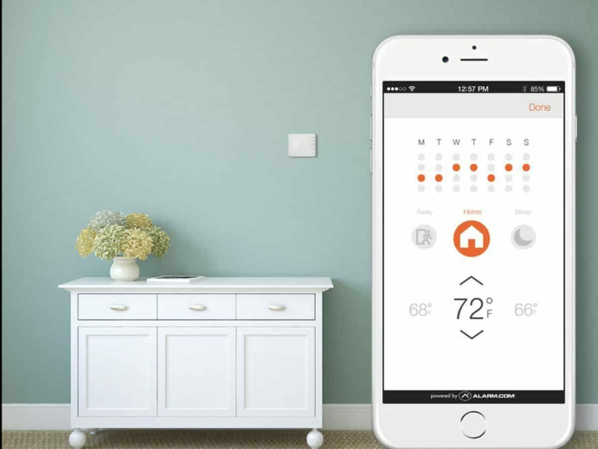 alarm.com smart home app against home wall
