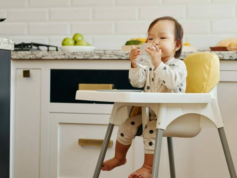 baby in a yellow high chair drinking out of sippy cup