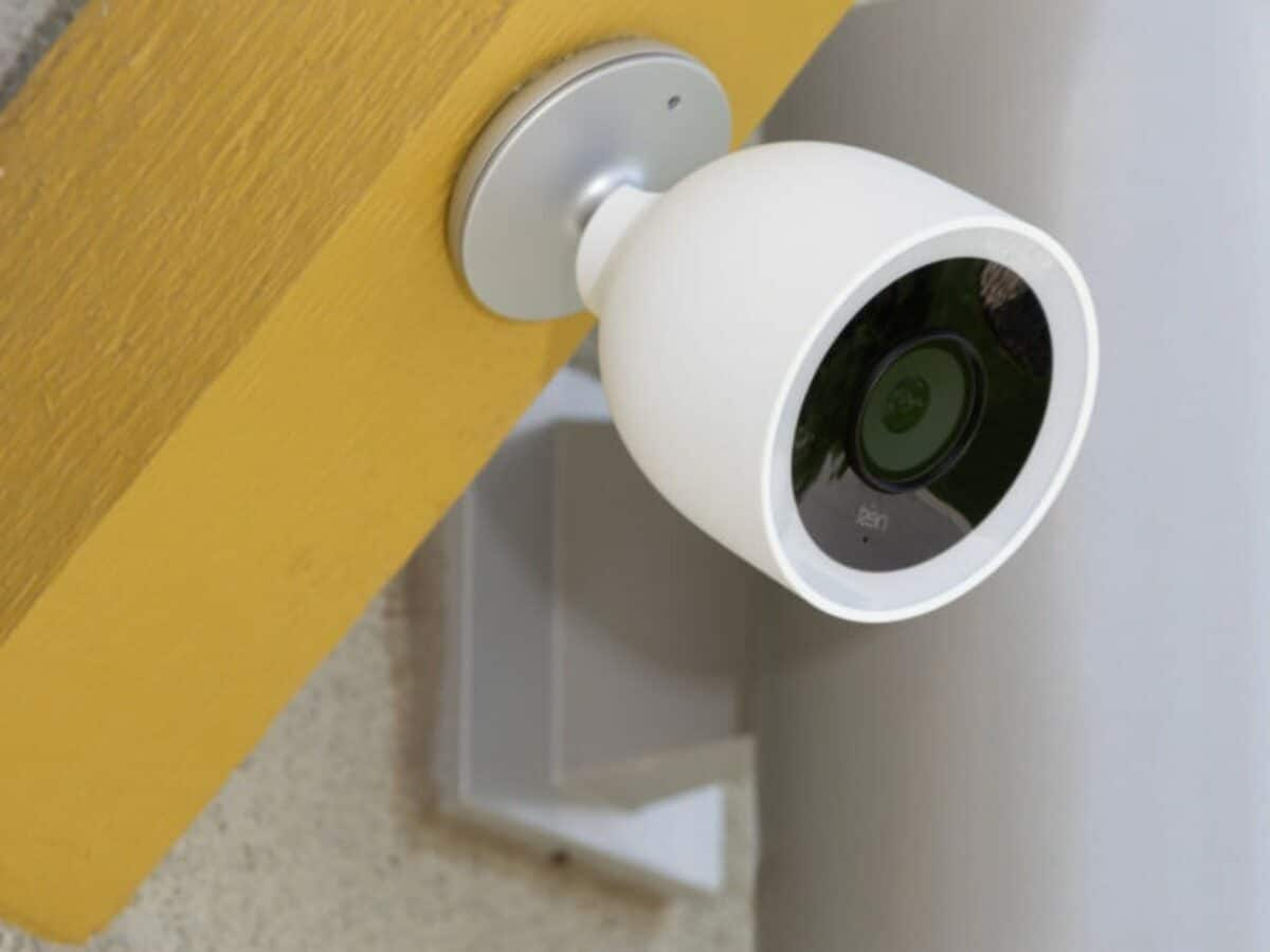 white security camera pointed left mounted on yellow wall